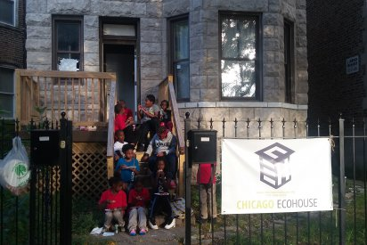 Participating youth sitting on the steps of Chicago Eco House. A sign on a wrought iron gage reads Chicago Eco House. Through the open gate entrance 10 children can be seen sitting on wooden steps up to a wooden deck off the the stone house, and beside its protruding bay window. The children are eating pizza.